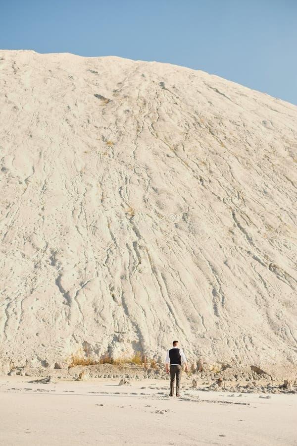Человек в костюме с солеными болотами против белой горы стоковые фотографии rf