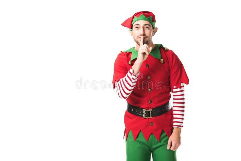 человек в костюме эльфа рождества показывая знак безмолвия hush и смотря изолированную камеру стоковые фотографии rf