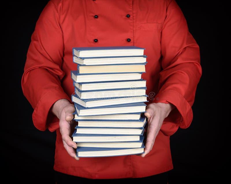 Человек в красной форме держит стог книг стоковые фото