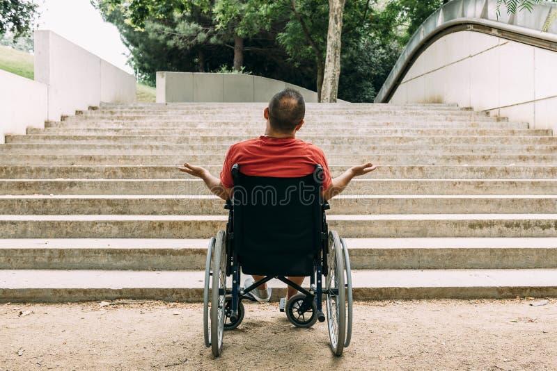 Человек в кресло-коляске злодействованной перед лестницами стоковое фото