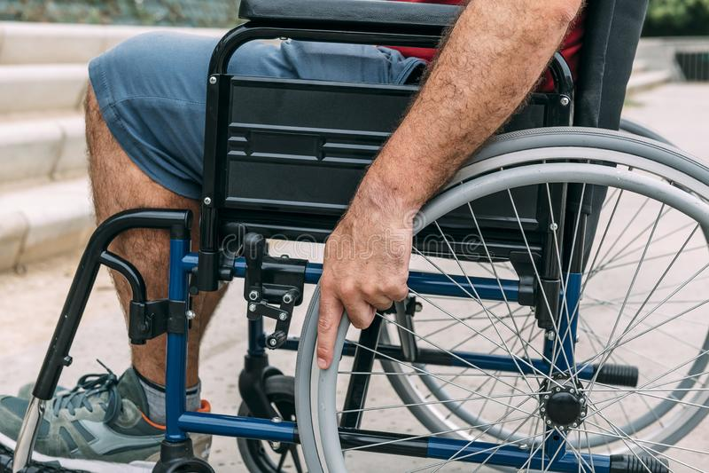 Человек в кресло-коляске с его рукой на колесе стоковые изображения rf