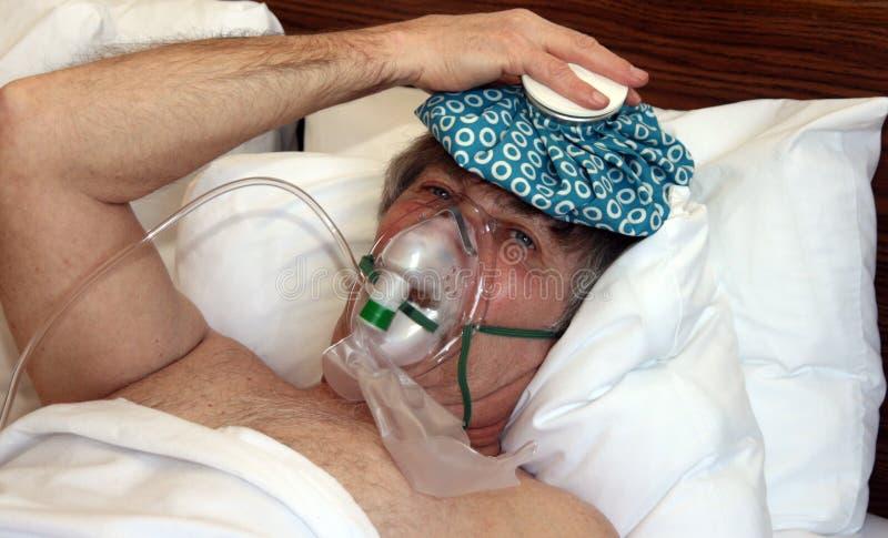 Человек в кровати с кислородным изолирующим противогазом стоковые изображения rf