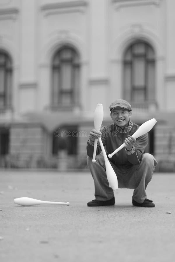 Человек в крышке демонстрирует жезлы в улице стоковая фотография rf