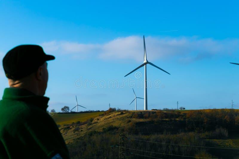 Человек в крышке смотрит закручивая ветротурбины против голубого неба стоковое изображение