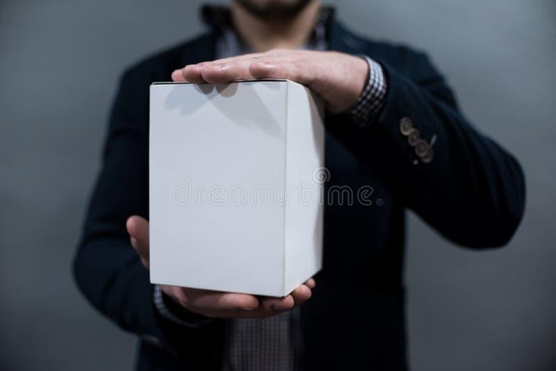 Человек в куртке и рубашке держа коробку белой бумаги стоковое фото