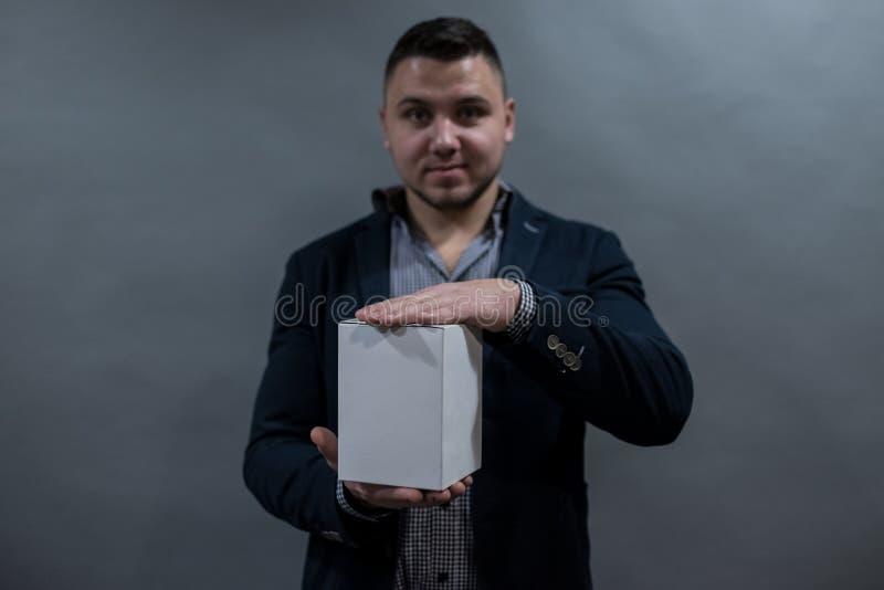 Человек в куртке и рубашке держа коробку белой бумаги стоковое фото rf