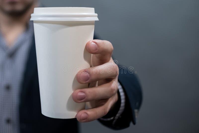 Человек в куртке и рубашке держа чашку белой бумаги пустая белизна для вашего текста стоковые фотографии rf
