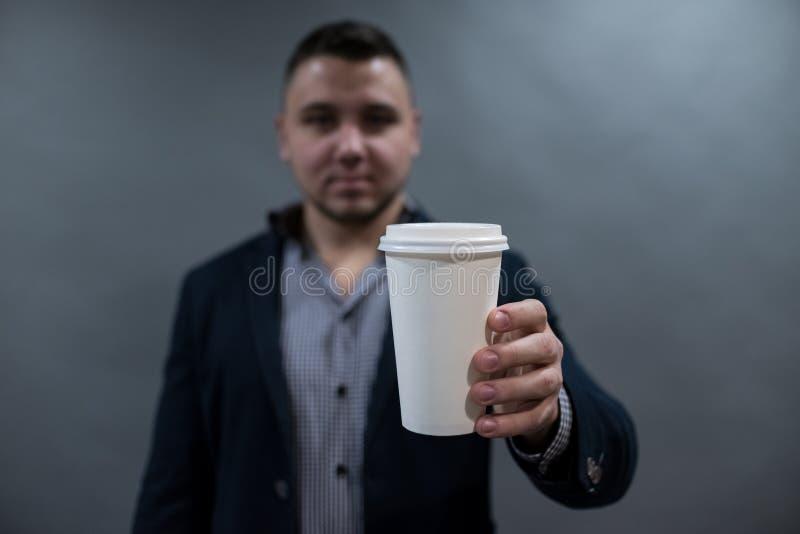 Человек в куртке и рубашке держа чашку белой бумаги пустая белизна для вашего текста стоковая фотография