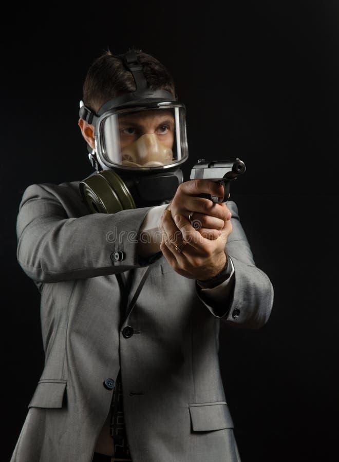 Человек в куртке костюма с оружием представляя как оперативный сотрудник стоковое изображение rf