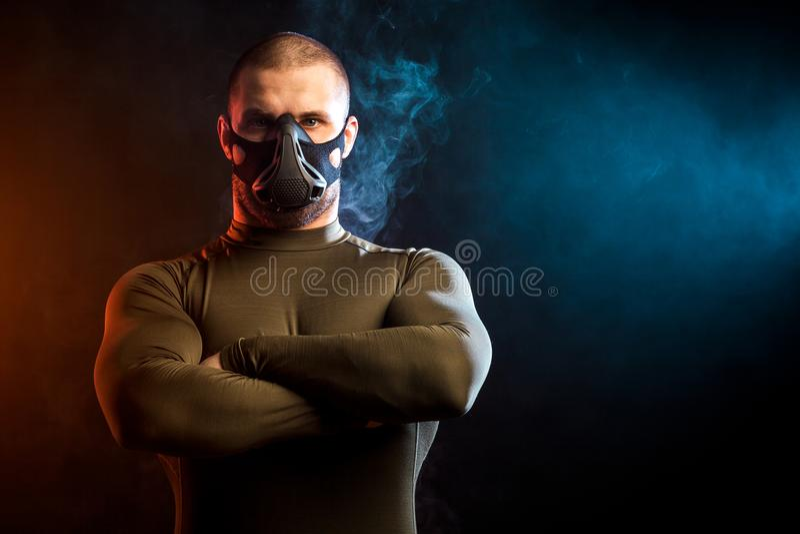 Человек в маске тренировки представляя на черноте стоковые фото