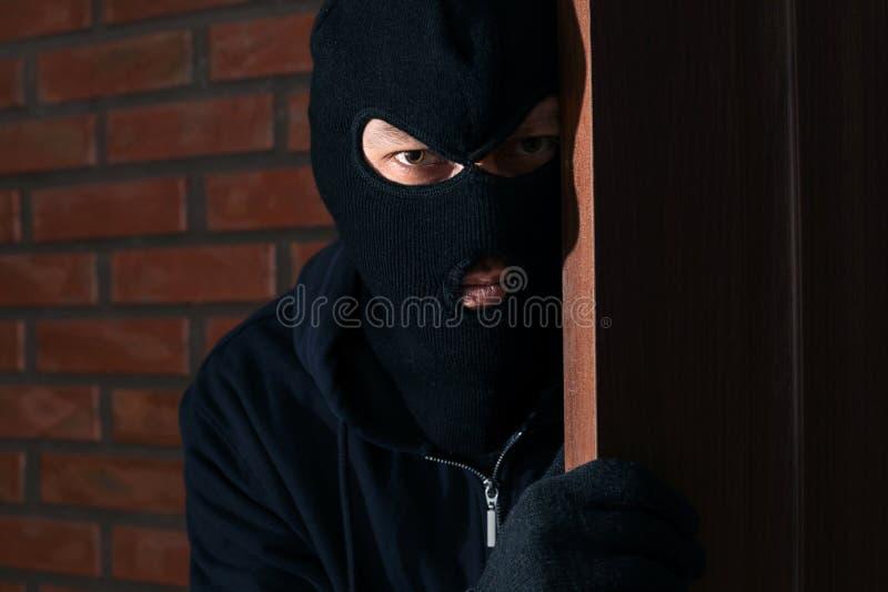 Человек в маске шпионя за дверью Преступная деятельность стоковые изображения