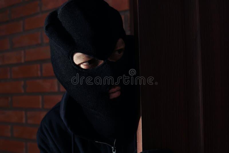 Человек в маске шпионя за дверью Преступная деятельность стоковые фото