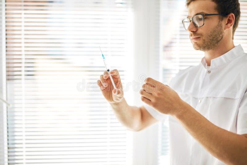 Человек в медицинской форме смотря шприц перед впрыской на рабочем месте стоковые изображения