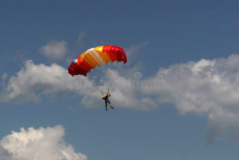 Человек в одеждах камуфлирования раскрыл парашют стоковое фото rf