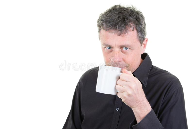 Человек в одежде офиса держа выпивая кружку кофе стоковая фотография