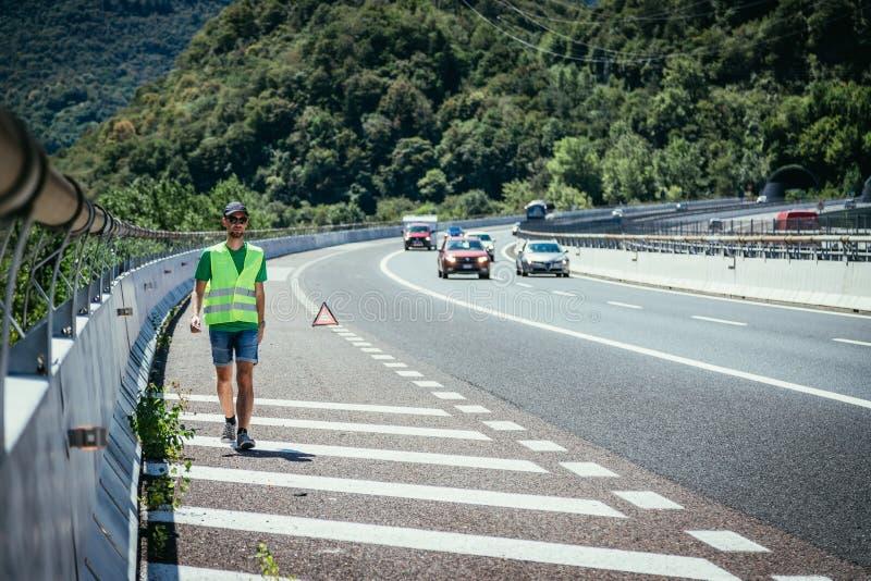 Человек в отражательном жилете аранжирует предупреждающий треугольник, нервное расстройство автомобиля на шоссе стоковые изображения