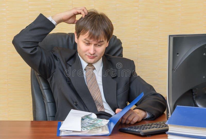 Человек в офисе царапая его голову, смотря конверт с деньгами в папке стоковая фотография