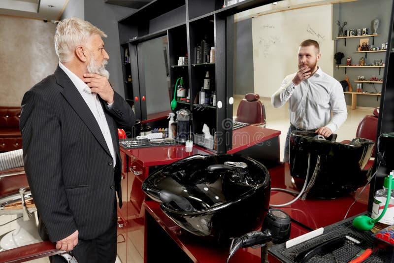 Человек в парикмахерскае видя на отражении зеркала молодого человека стоковое изображение rf