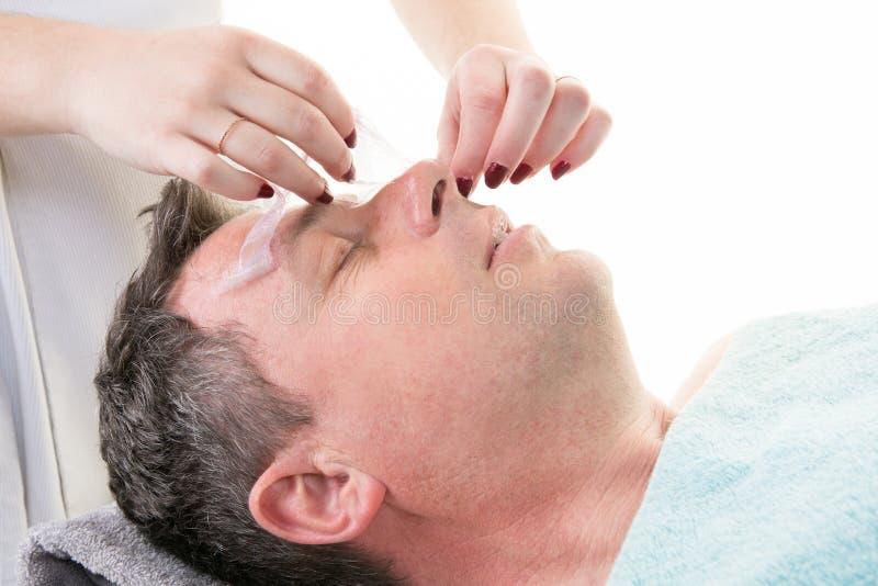 Человек в процедуре по маски косметической в курорте стоковые изображения rf