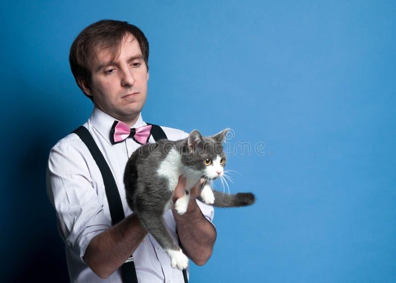 Человек в розовой рубашке и бабочке держа и смотря милого серого и белого кота стоковое изображение