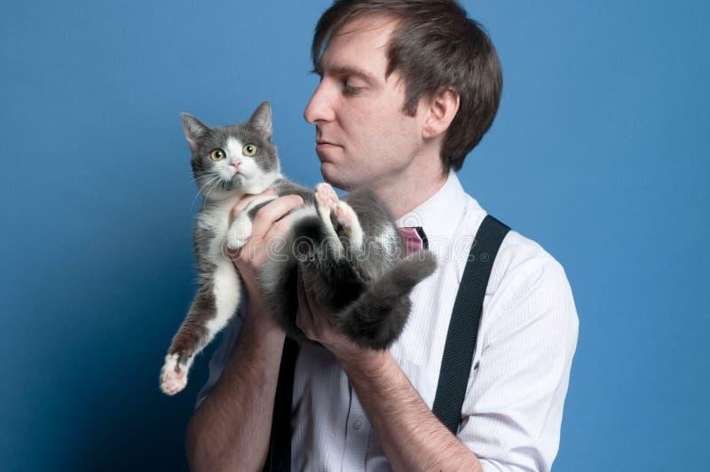 Человек в розовой рубашке и черном подтяжк держа и смотря милого серого и белого кота стоковое изображение
