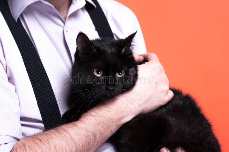 человек в рубашке держа милого черного кота перед предпосылкой коралла стоковое изображение