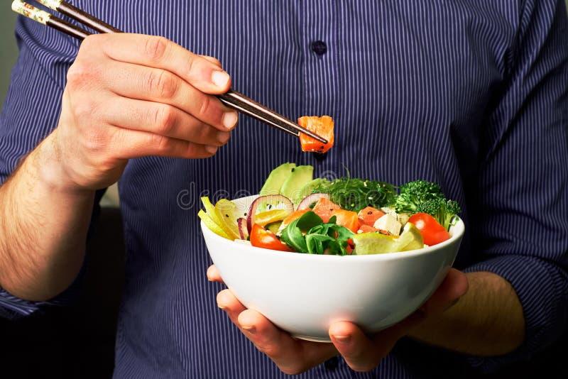 человек в рубашке держит засовывает шар с семгами, авокадоом, огурцами, arugula, брокколи, рисом, морковами, сыром и chuha с пало стоковое изображение rf