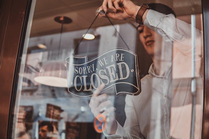 Человек в рубашке кладет nameplate о закрывать на его собственный магазин стоковые изображения rf