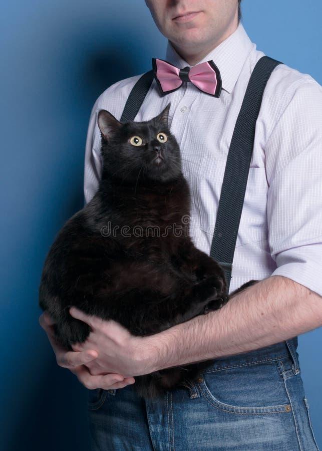 Человек в рубашке, подтяжк и розовой бабочке держа милого черного кота смотря вверх на голубой предпосылке стоковое фото rf