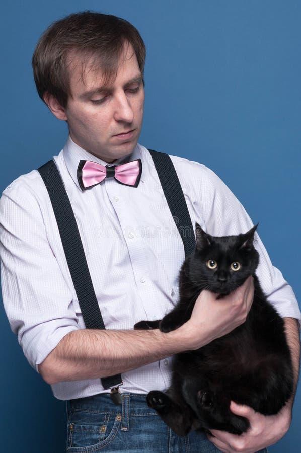 Человек в рубашке, подтяжк и розовой бабочке держа и смотря к милому черному коту на голубой предпосылке стоковое фото rf