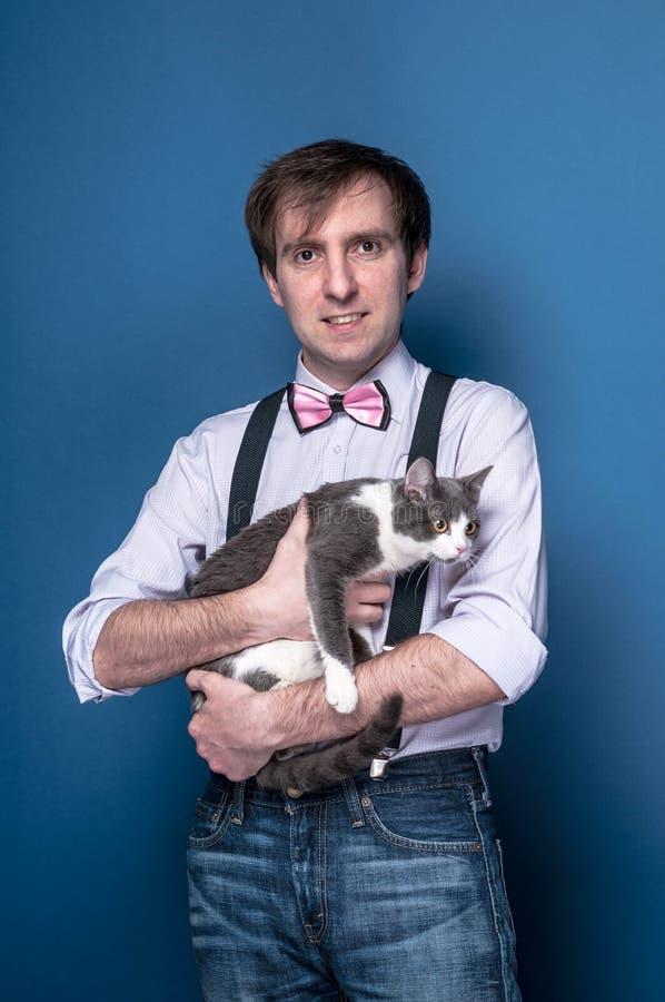 человек в рубашке, подтяжк и розовой бабочке смотря камеру, усмехаясь и держа милого серого кота стоковое фото