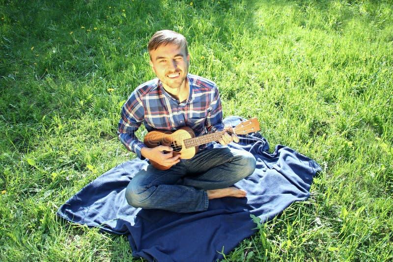 Человек в рубашке шотландки сидя в парке с гавайской гитарой стоковое фото