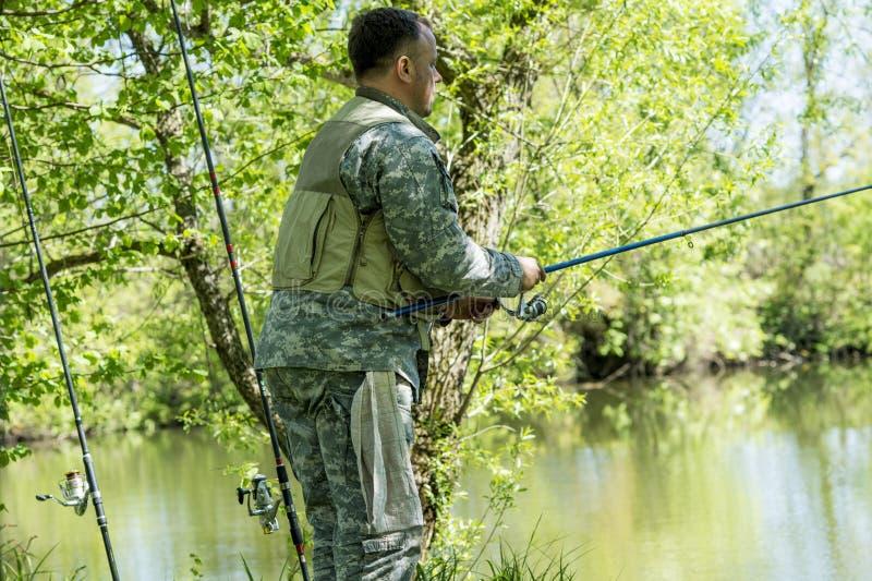 Человек в рыболовной удочке камуфлирования на речном береге в раннем лете стоковое фото rf
