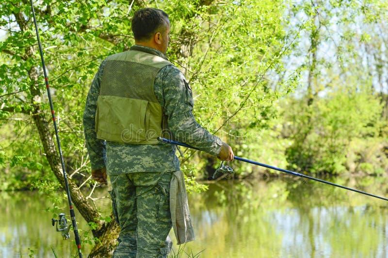 Человек в рыболовной удочке камуфлирования на речном береге в раннем лете стоковое изображение rf