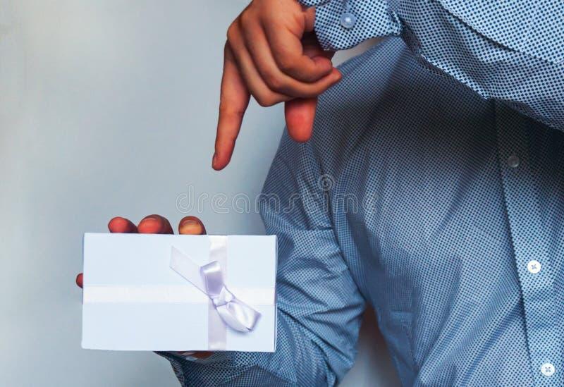 Человек в светлой рубашке держит белую подарочную коробку с лентой сирени в его руке тонизировать стоковые изображения