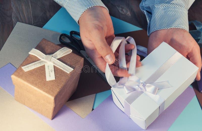 Человек в светлой рубашке подготавливает подарочную коробку на праздник тонизировать стоковое изображение rf