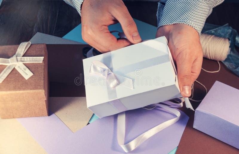 Человек в светлой рубашке подготавливает подарочную коробку на праздник тонизировать стоковые изображения rf