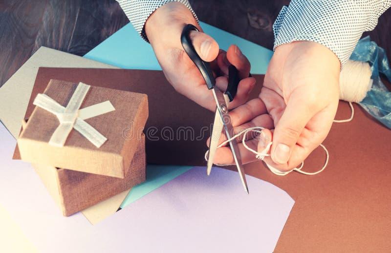Человек в светлой рубашке подготавливает подарочную коробку на праздник тонизировать стоковые изображения