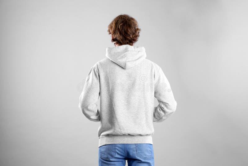 Человек в свитере hoodie на светлой предпосылке стоковое фото rf