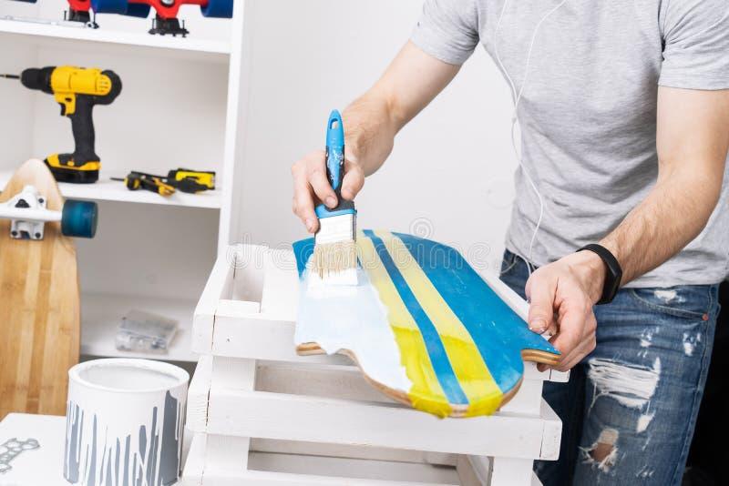 Человек в серой футболке красит доску скейтборда в мастерской и слушает к музыке на наушниках стоковая фотография rf