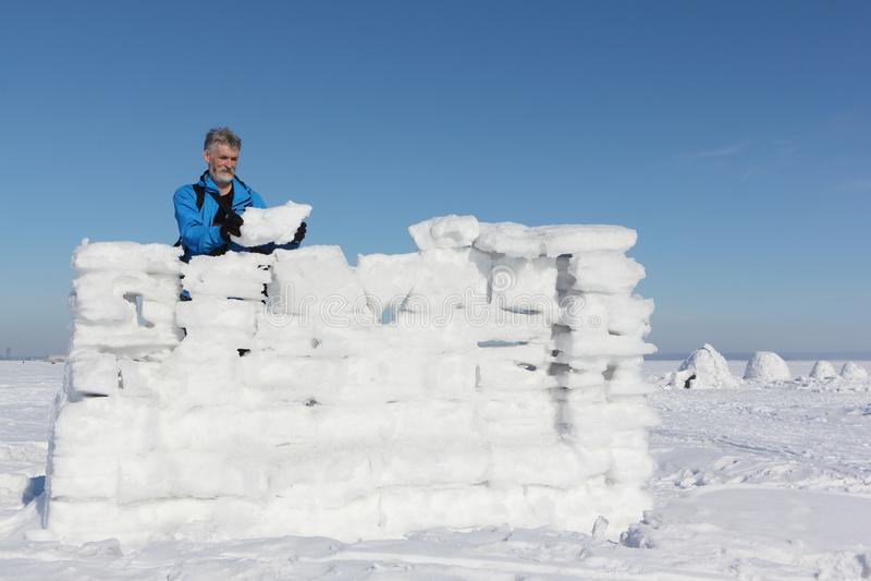 Человек в синем пиджаке строя стену снега стоковые изображения