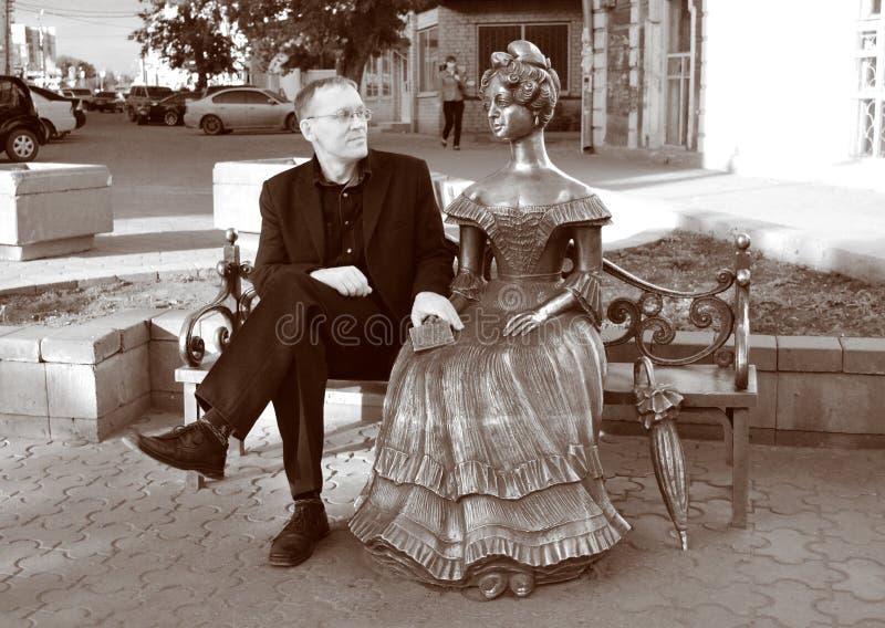 Человек в стеклах, сидит на стенде близко к женской скульптуре стоковые фото
