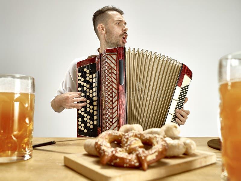 Человек в традиционных баварских одеждах играя аккордеон oktoberfest стоковая фотография
