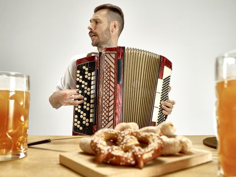 Человек в традиционных баварских одеждах играя аккордеон oktoberfest стоковое фото