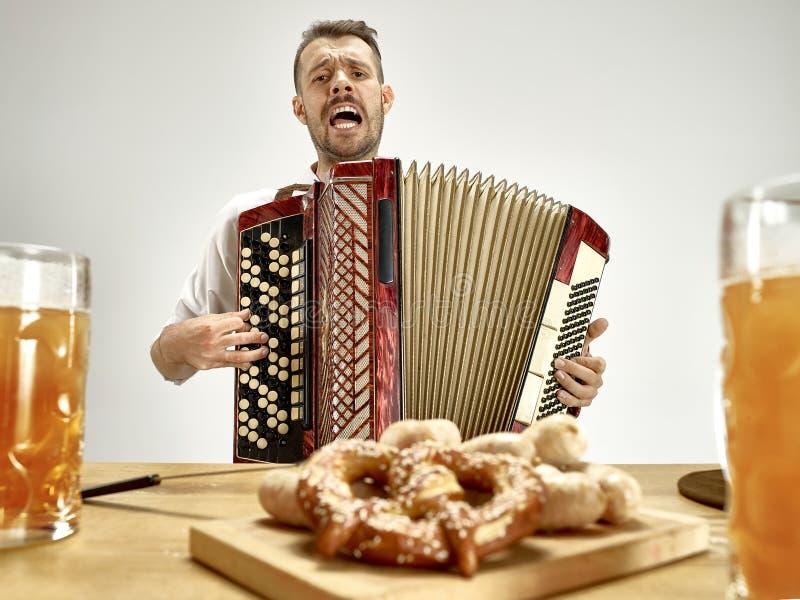 Человек в традиционных баварских одеждах играя аккордеон oktoberfest стоковая фотография rf