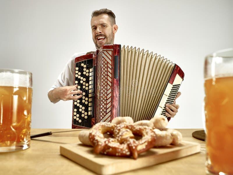 Человек в традиционных баварских одеждах играя аккордеон oktoberfest стоковые фото