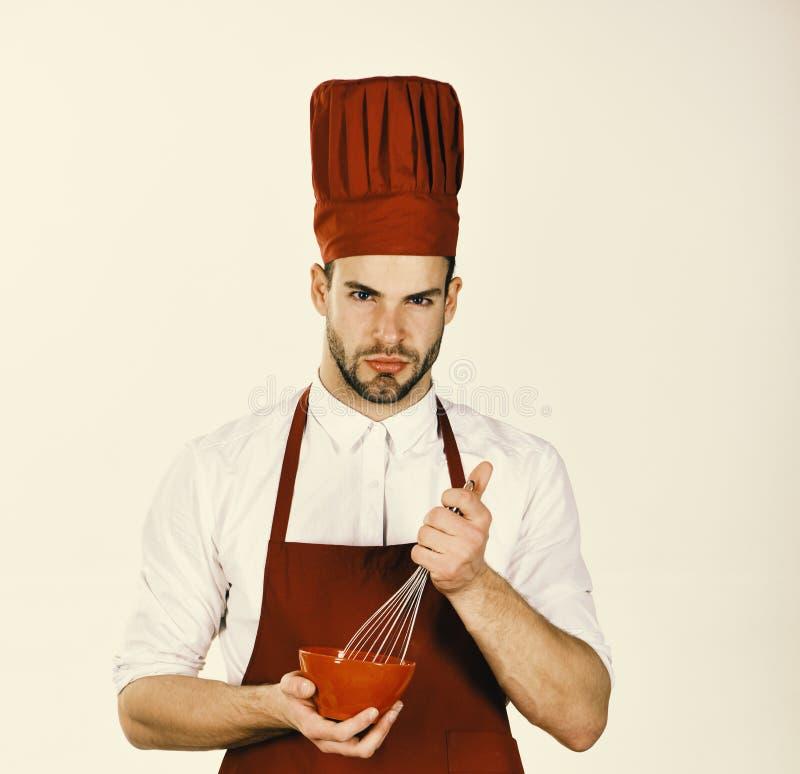 Человек в форме кашевара держит kitchenware Шеф-повар с серьезной стороной стоковые изображения rf