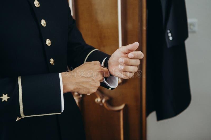 Человек в форме регулируя вахту в его запястье руки стоковое изображение