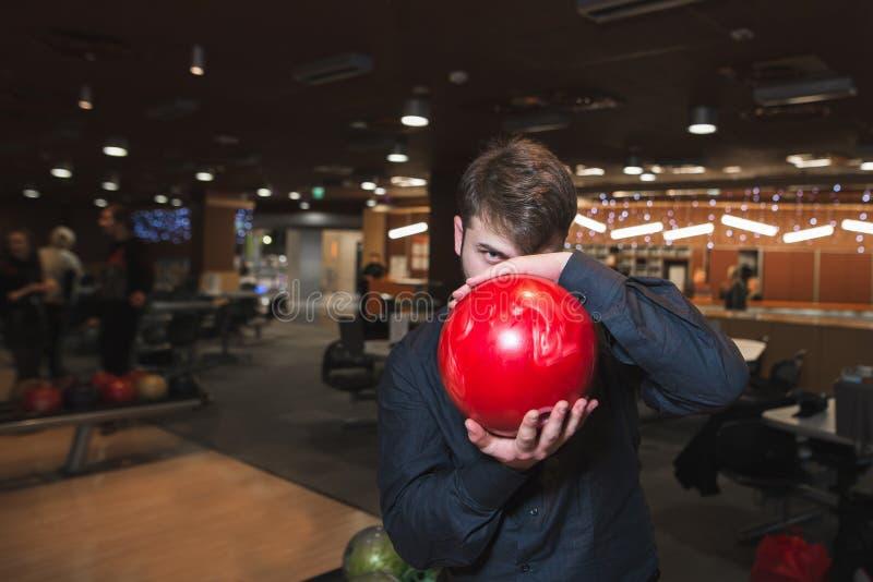 Человек в черной рубашке держит шар для его стороны и смотрит и ищет его стоковое изображение