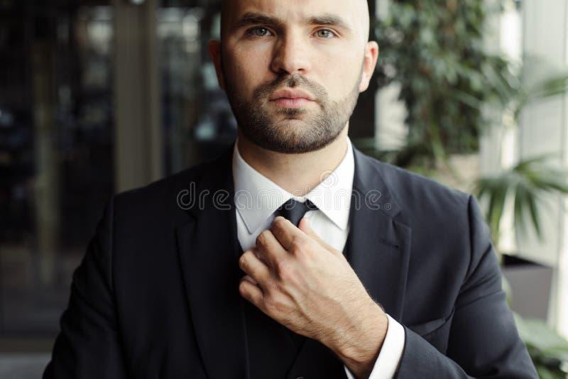 Человек в черном костюме выправляет его связь стоковая фотография rf
